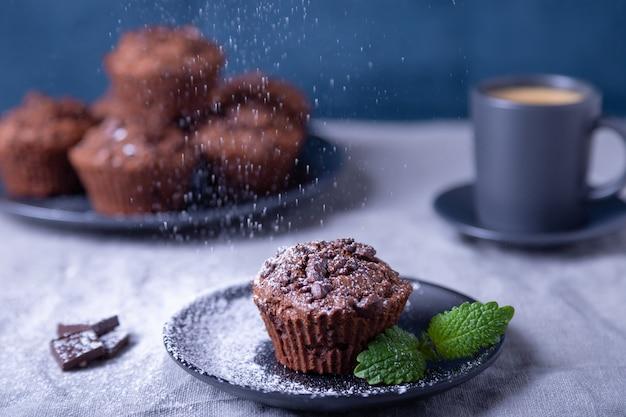 Magdalenas de chocolate con menta en un plato negro, con azúcar glas. horneado casero. en el fondo hay una taza de café y un plato con magdalenas. fondo azul. Foto Premium