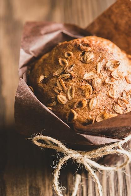 Magdalenas con copos de trigo en papel marrón embalaje primer plano fondo de madera. postre vegano saludable. Foto Premium