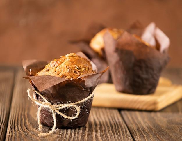 Magdalenas con copos de trigo en papel marrón embalaje primer plano fondo de madera. Foto Premium