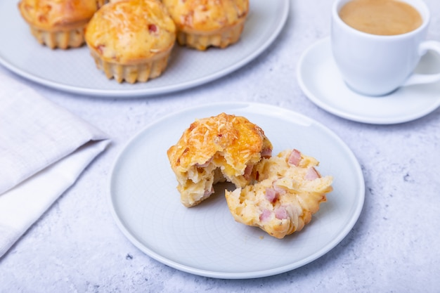 Magdalenas con jamón y queso. horneado casero. en el fondo hay un plato con magdalenas y una taza de café. de cerca. Foto Premium