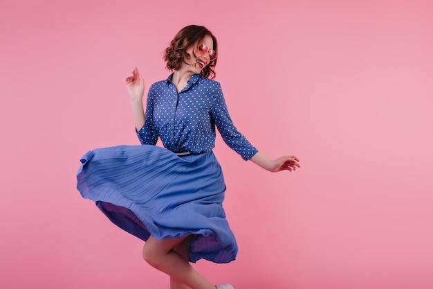 Magnífica modelo femenina en falda midi bailando y riendo en la pared rosa. mujer caucásica emocionada en ropa azul que expresa emociones positivas. Foto gratis