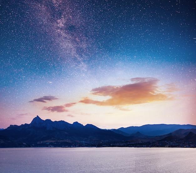 Magnífico panorama del amanecer sobre el mar. cielo nocturno vibrante con estrellas y nebulosa y galaxia. astrofotografía de cielo profundo Foto Premium