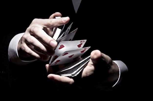 Mago barajando las cartas de una manera genial bajo el reflector Foto gratis