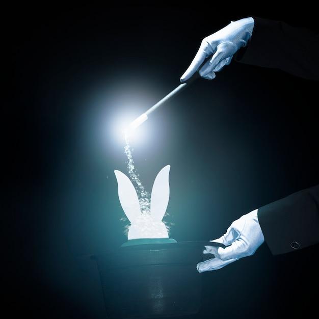 Mago realizando truco con varita mágica sobre fondo negro brillante Foto gratis