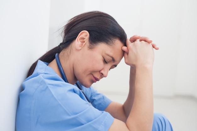 Malestar enfermera sentada en el piso Foto Premium