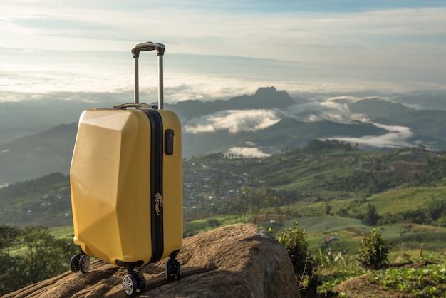 Maleta de viaje sobre la naturaleza del bello paisaje de montaña y la niebla. Foto Premium