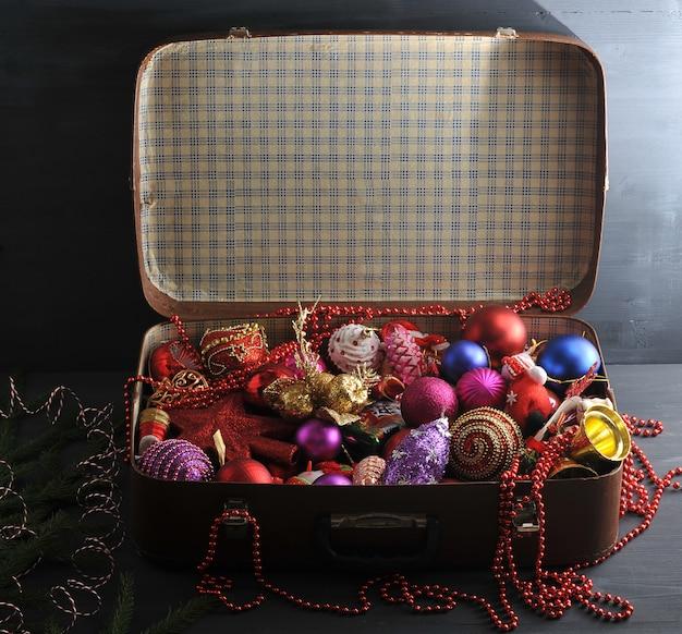 Maleta vintage con decoraciones festivas de navidad para el árbol de navidad. Foto Premium