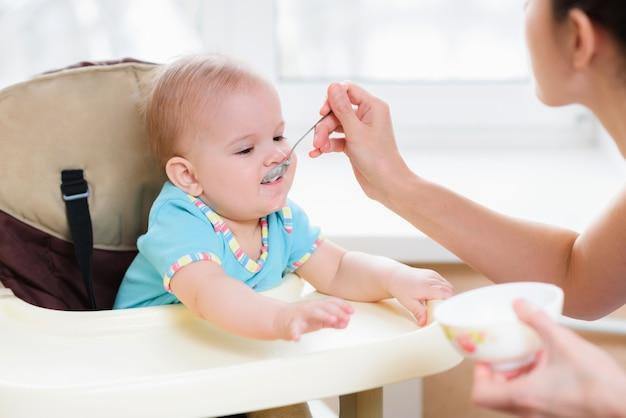 Mamá alimenta a su bebé de nueve meses en casa Foto Premium