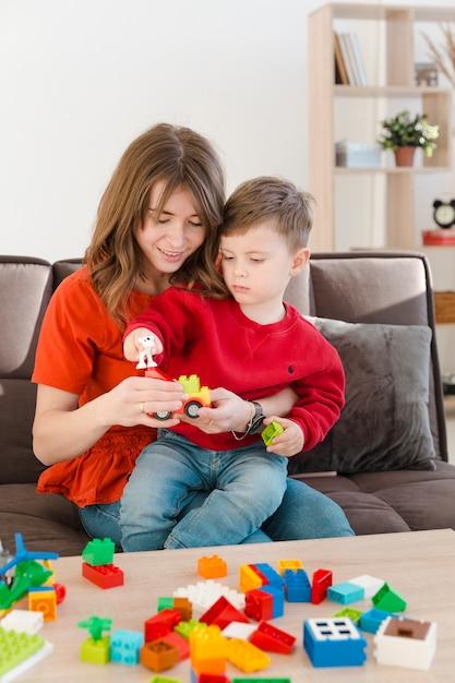 Mamá ayudando a hijo a jugar Foto gratis