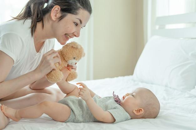 Mamá y bebé felizmente se burlan mutuamente en una cama blanca. Foto gratis