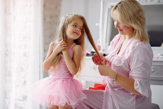 Mamá e hija en casa con rulos en la cabeza Foto gratis