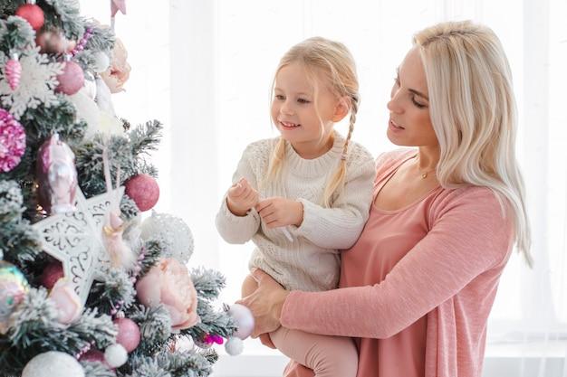 Mamá e hija decoran el árbol rosado de navidad en el interior. Foto Premium