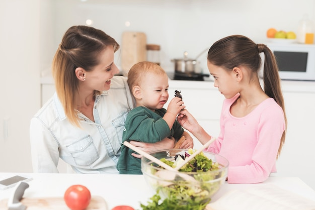 Mamá e hija se divierten mientras preparan una ensalada. Foto Premium