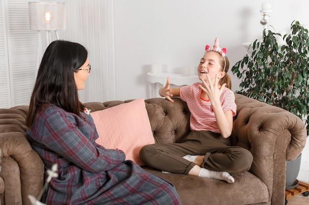Mamá e hija están sentadas en el sofá y charlando Foto Premium