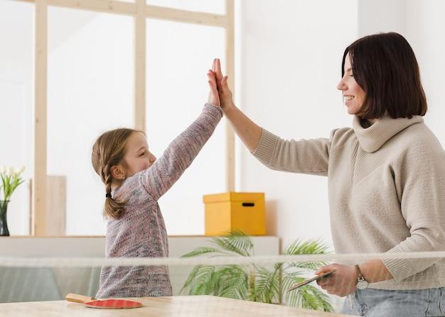 Mamá e hija haciendo chocar los cinco Foto gratis