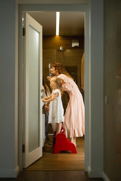 Mamá e hijas hacen maquillaje en el baño, aplican lápiz labial frente al espejo. Foto gratis