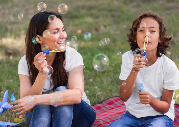 Mamá e hijo haciendo globos juntos al aire libre Foto gratis