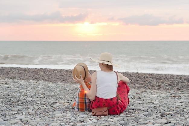 Mamá e hijo juegan en la playa de guijarros. Foto Premium