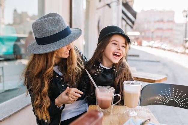 Mamá elegante e hija muy sonriente disfrutando juntos el fin de semana en un restaurante al aire libre tomando café y batido. Foto gratis