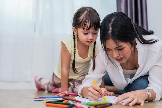 Mamá enseñando a su hija a dibujar en la clase de arte. regreso a ...