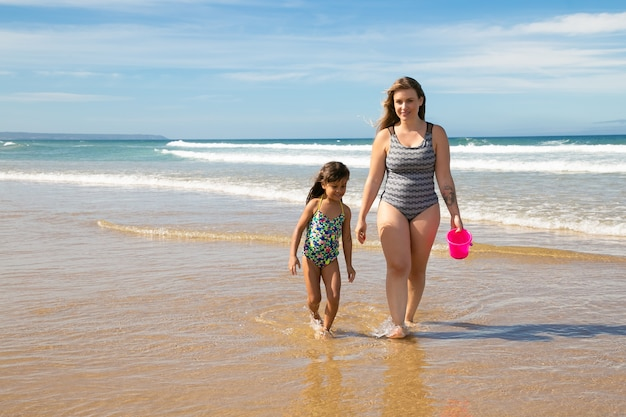 Mamá feliz y niña vistiendo trajes de baño, caminando hasta los tobillos en el agua de mar en la playa Foto gratis