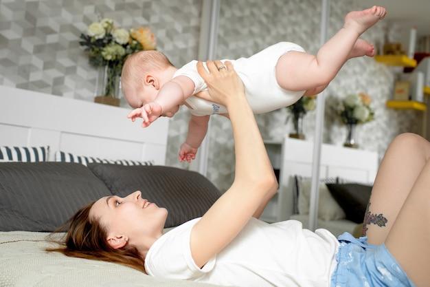 Mamá juega con el bebé 6 meses en la cama en casa Foto Premium