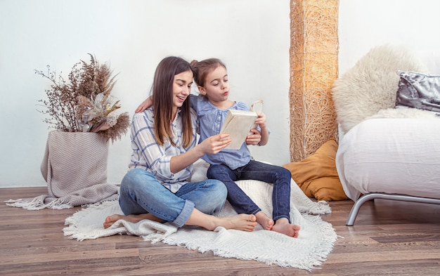 Mamá lee un libro con sus hijas en casa. Foto gratis