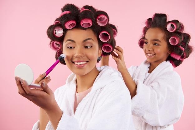 Mamá lleva belleza mientras la niña se trenza el pelo. Foto Premium