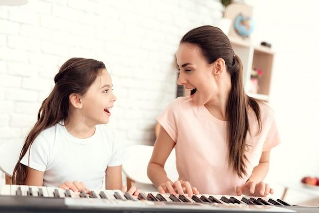 Mamá y niña están tocando el sintetizador juntas. Foto Premium