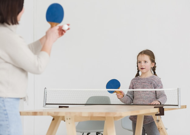 Mamá y niño jugando ping pong Foto gratis