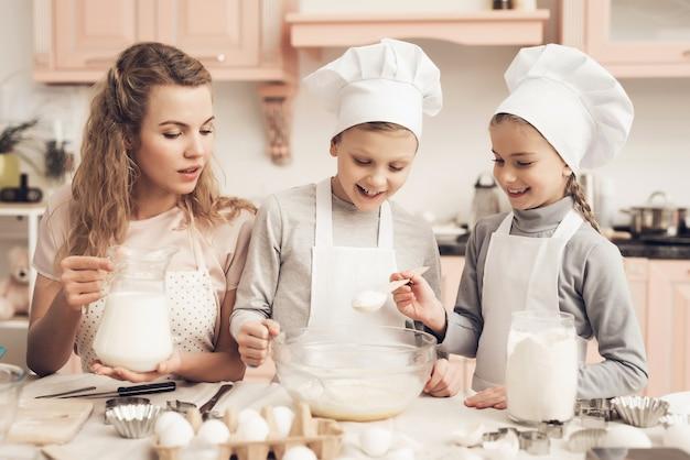 Mamá y niños haciendo una masa happy girl agrega azúcar. Foto Premium