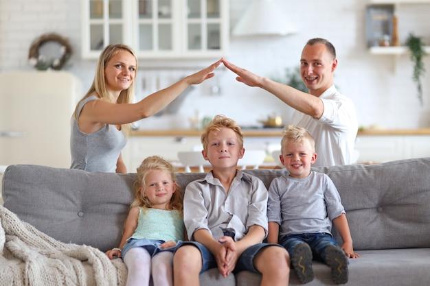 Mamá y papá haciendo figura del techo con las manos brazos sobre tres niños hads. concepto de vivienda. Foto Premium