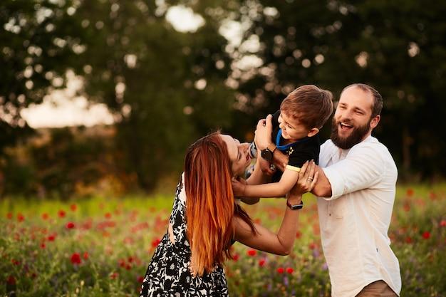 Mamá y papá sostienen a su pequeño hijo en los brazos que se colocan en el campo verde con amapolas Foto gratis