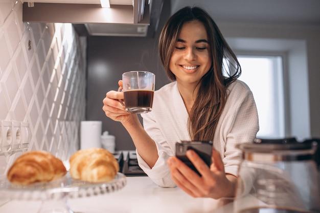 Mañana de la mujer con teléfono, croissant y café en la cocina. Foto gratis