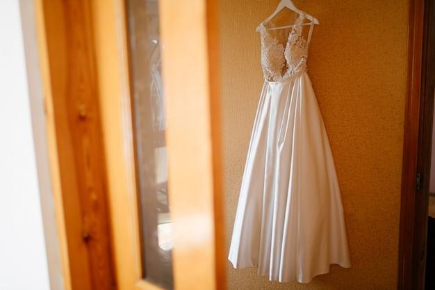 Mañana de la novia cuando ella lleva un hermoso vestido. Foto gratis