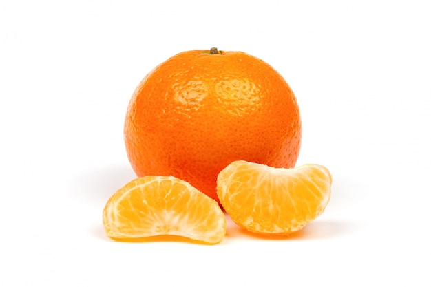 Mandarina madura en cáscara y rodajas de mandarina peladas primer plano aislado Foto Premium