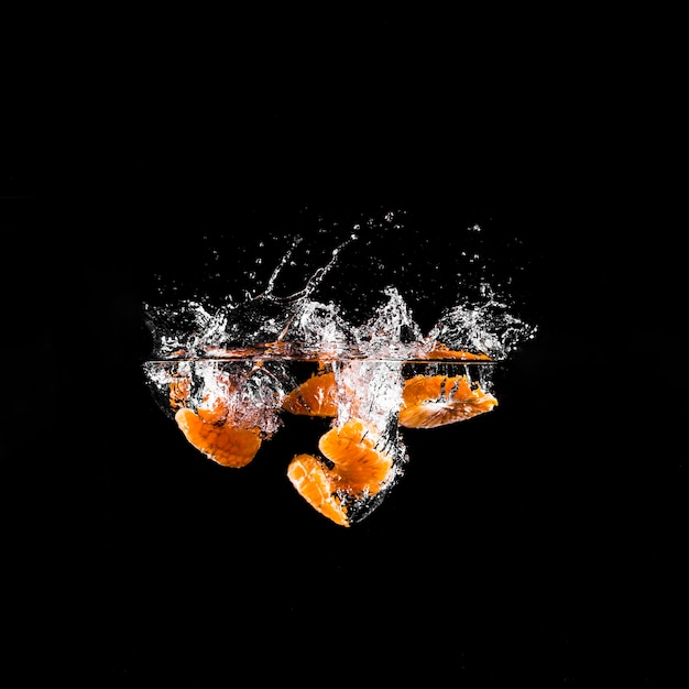 Mandarina sumergiéndose en el agua Foto gratis