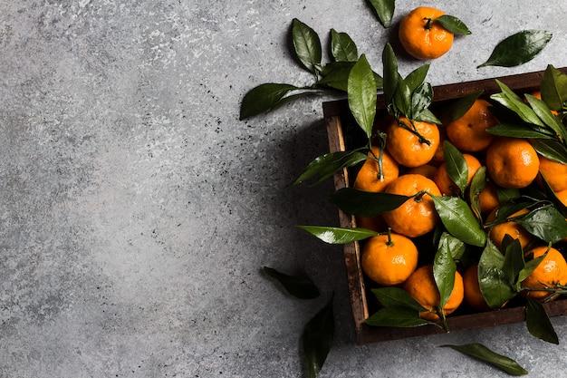 Mandarinas con hojas verdes en caja de madera sobre luz Foto gratis