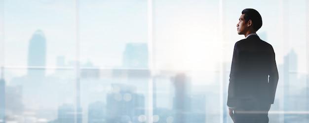 Manera comercial exitosa, cómo tener éxito y ser un logro y enfocarse en el concepto de meta, joven empresario de pie y mirando para desarrollar la vida laboral para el líder en la cima de la ciudad Foto Premium