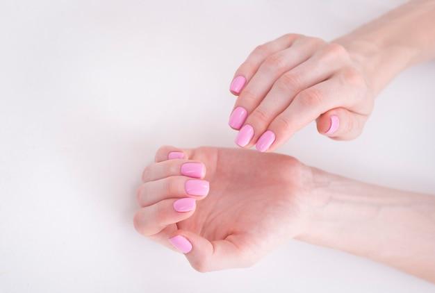 Manicura rosa suave en manos femeninas Foto Premium