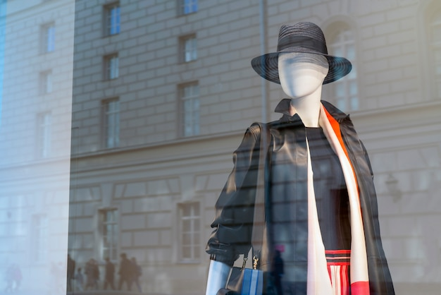 Maniquí en la ventana de la tienda detrás del cristal. Foto Premium