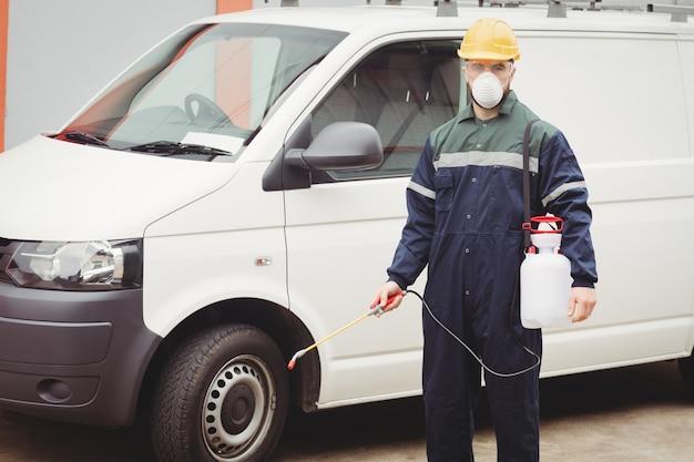 Manitas con insecticida parado frente a su camioneta Foto Premium