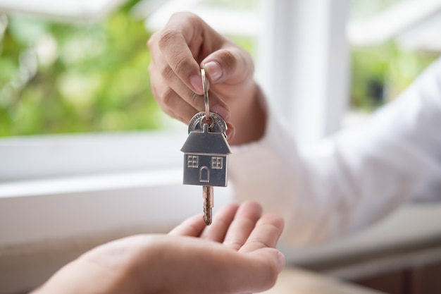 Mano del agente de bienes raíces que da las llaves de una casa al comprador de la casa. Foto Premium
