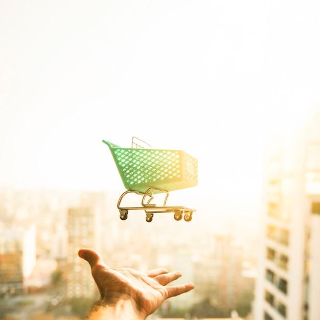 Mano alcanzando para carrito de supermercado en el fondo borroso Foto gratis