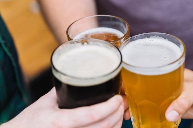 La mano de un amigo tostando un vaso de bebidas alcohólicas Foto gratis