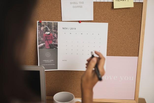 Mano anotando planes importantes en el calendario Foto gratis