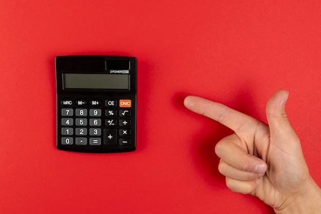 Mano apuntando a una mini calculadora Foto gratis