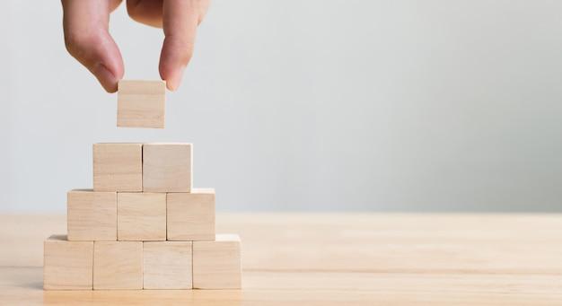 Mano arreglando el apilamiento de bloques de madera como escalón. concepto de negocio para el proceso de crecimiento exitoso Foto Premium