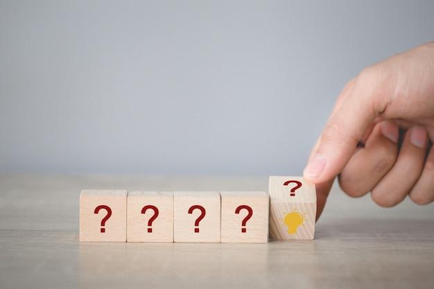 Mano arreglando voltea apilamiento de bloque de madera con icono de signo de interrogación y lámpara, pensando con el concepto de signo de interrogación. Foto Premium