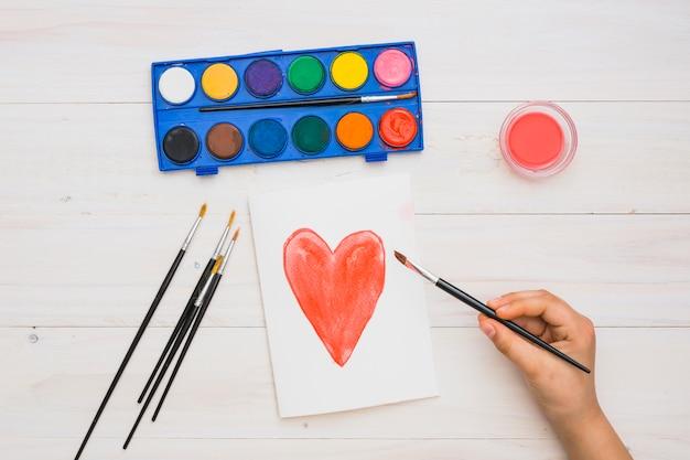 La mano del artista que sostiene el pincel en la mano dibujada forma de corazón pintura sobre superficie de madera Foto gratis